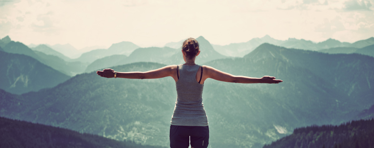 young female standing on mountain top with her arms outstretched