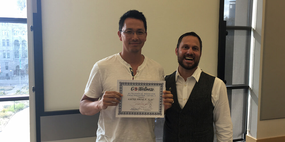 Regan poses with GoWellness Practitioner holding a certificate of completion for GoWellness Training
