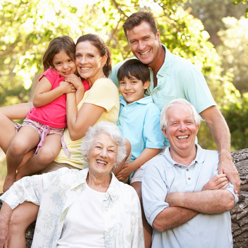 multi-generational family smiling in an outdoor setting